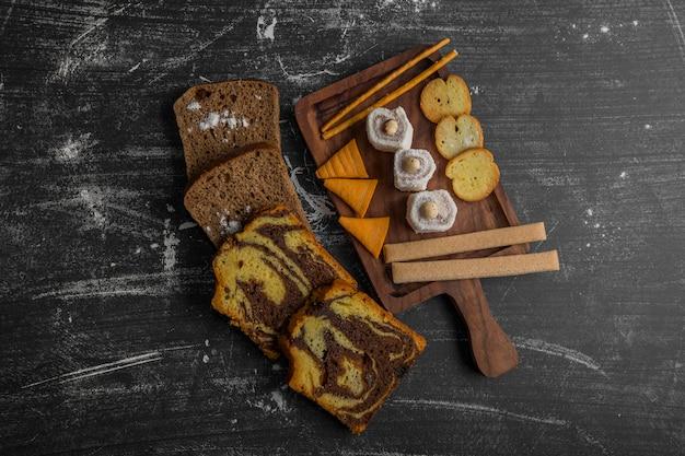 Batata frita com produtos de confeitaria em uma travessa de madeira e fatias de pão à parte no meio