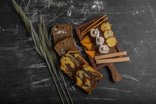 Batata frita com produtos de confeitaria em uma travessa de madeira e fatias de pão à parte, vista de cima