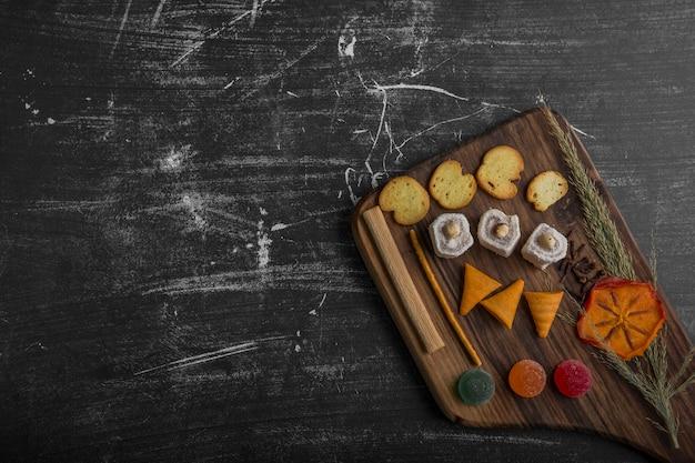 Batata frita com produtos de confeitaria em uma travessa de madeira no canto inferior