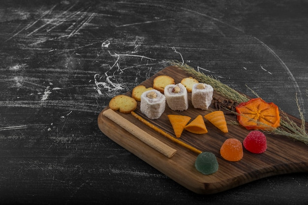 Batata frita com produtos de confeitaria em uma travessa de madeira, vista angular