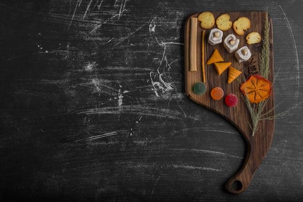 Batata frita com produtos de confeitaria em uma travessa de madeira, vista superior