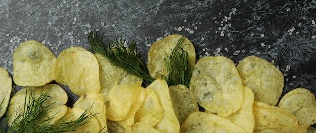 Batata frita com sal e endro na superfície preta esfumada