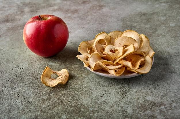 Batata frita de maçã desidratada no prato e maçã no fundo de madeira close-up
