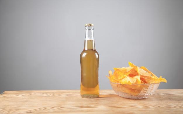 Batata frita e garrafa de cerveja na mesa de madeira.