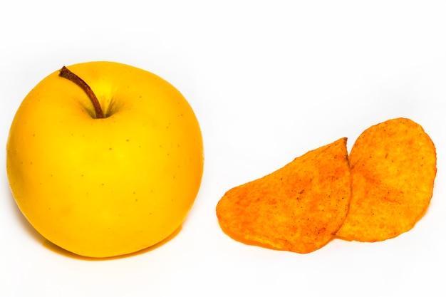 Batata frita e uma maçã, o conceito de escolher o alimento certo, isolado no fundo branco.