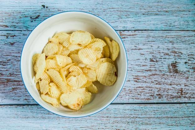 Batata frita na tigela branca e fora tigela sobre a cor de tinta azul madeira grunge