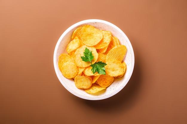 Batata frita ondulada dourada com folha de salsa em uma tigela de madeira com fundo marrom, vista superior