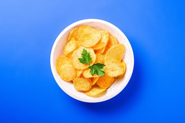 Batata frita ondulada dourada com folha de salsa em uma tigela de madeira sobre fundo azul, vista superior