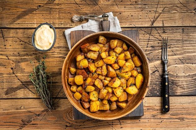 Batata frita - patatas bravas batatas tradicionais espanholas petiscos de tapas. fundo de madeira. vista do topo.