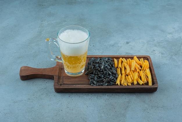 Batata frita, sementes de girassol e um copo de cerveja em uma placa, sobre o fundo azul.