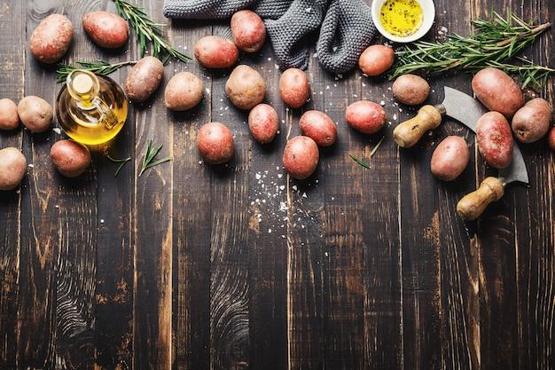 Batata orgânica crua com especiarias na mesa de madeira