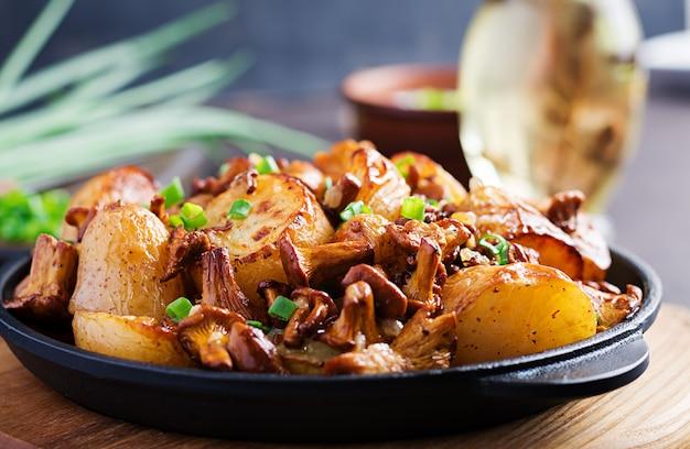 Batatas assadas com alho, ervas e chanterelles fritos em uma frigideira de ferro fundido.