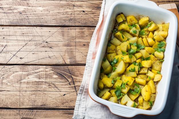 Batatas assadas com especiarias e ervas em uma assadeira de cerâmica. cozinha vegetariana. espaço da cópia