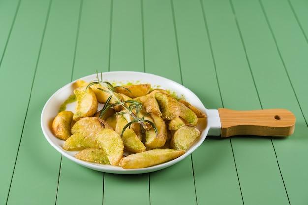 Batatas assadas com molho verde e alecrim em um prato branco em forma de frigideira. batatas fritas com molho pesto sobre uma mesa verde.