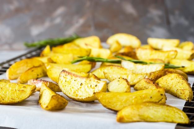 Batatas assadas em uma assadeira com pedaços de especiarias e alecrim