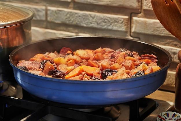 Batatas, cenouras, presunto e alho preto são fritos na frigideira.