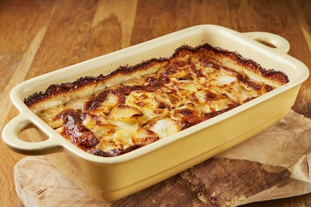 Batatas com cogumelos em formato especial num suporte de madeira depois de assadas no forno. receita passo a passo.