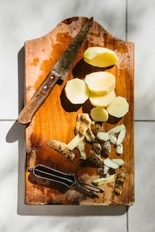 Batatas cortadas com faca na tábua de madeira