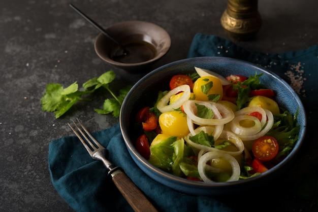 Batatas cozidas com cebola e legumes em um prato, prato tradicional russo, copie o espaço