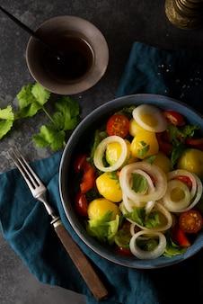 Batatas cozidas com cebola e legumes em um prato, prato tradicional russo, vista de cima