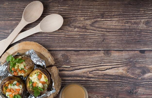 Batatas cozidas com diferentes ingredientes em fundo de madeira