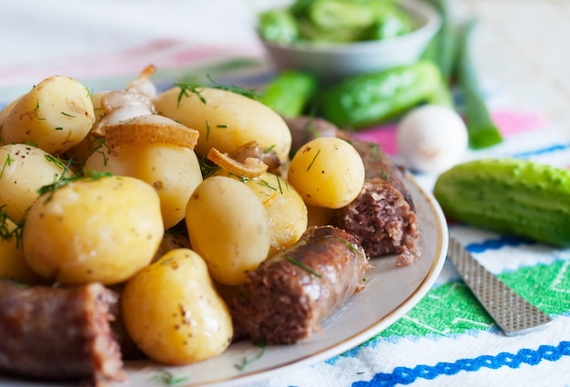 Batatas cozidas com fatias de salsicha grelhada foto do close up.