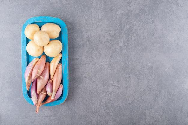 Batatas cruas com alho em uma tábua de madeira azul