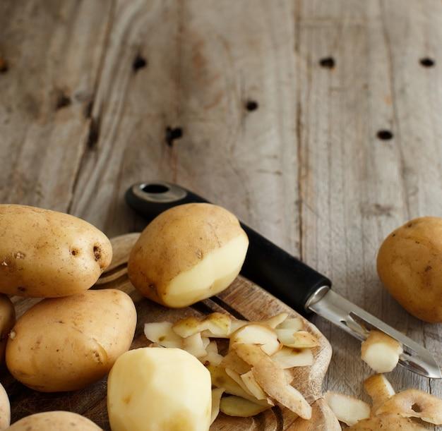 Batatas cruas com descascador de vegetais vista superior