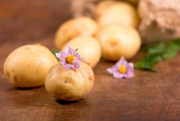 Batatas cruas com flores no fundo de madeira