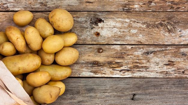 Batatas cruas derramando de um saco de papel reciclado em placas de madeira.