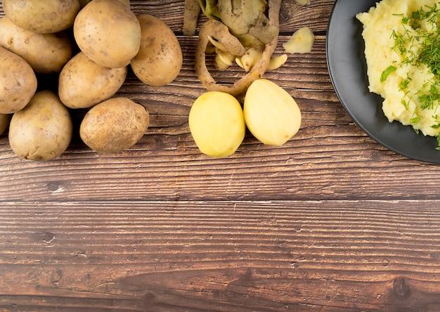 Batatas cruas em fundo de madeira com espaço de cópia