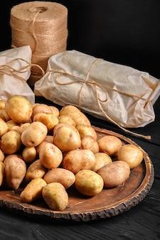 Batatas cruas em fundo de madeira preto rústico.