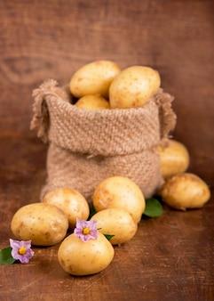 Batatas cruas em saco de aniagem, isoladas em uma mesa de madeira
