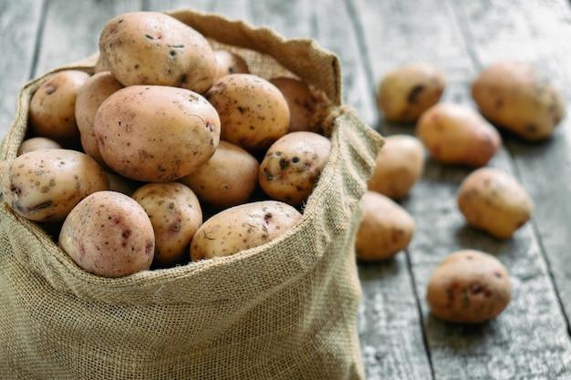Batatas cruas em um saco de estopa sobre as tábuas de madeira ásperas