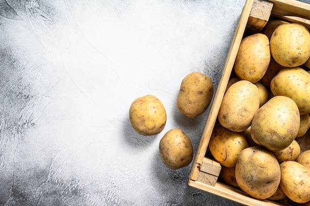 Batatas cruas em uma caixa de madeira velha em uma tabela.