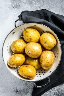 Batatas cruas lavadas em uma peneira