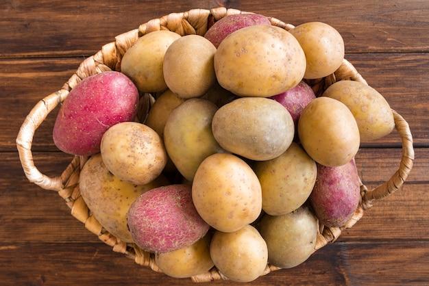 Batatas cruas na cesta de madeira