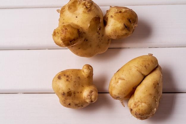 Batatas curvadas feias na moda no fundo de madeira branco.