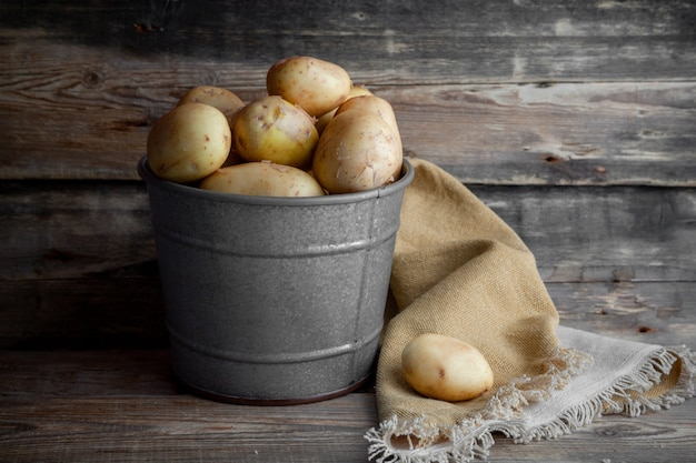Batatas da vista lateral no balde cinza no fundo escuro de madeira. horizontal