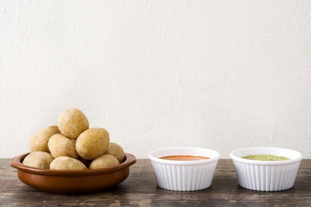 Batatas das canárias (papas arrugadas) com molho mojo na mesa de madeira
