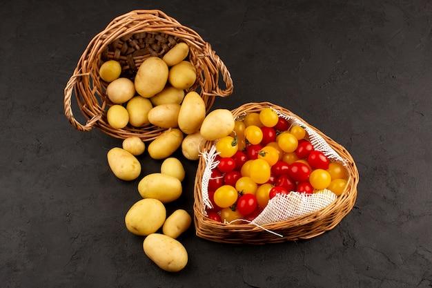 Batatas de vista superior, juntamente com tomates vermelhos e amarelos dentro de cestas na mesa cinza