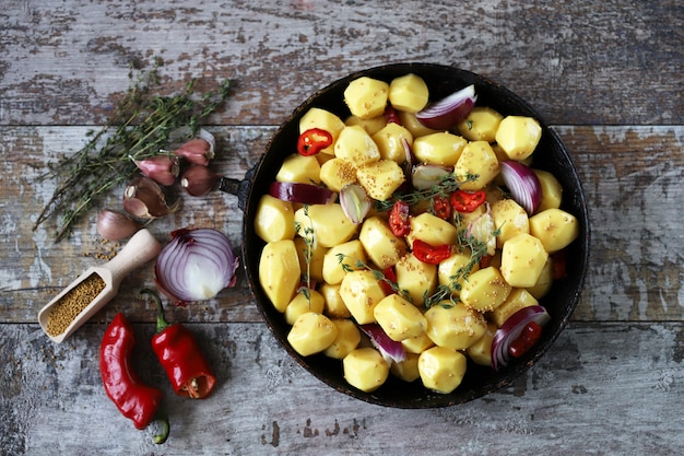 Batatas descascadas cruas inteiras em uma panela com temperos, ervas e alho antes de assar. cozinhar batatas assadas. foco seletivo.