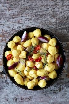 Batatas descascadas cruas inteiras em uma panela com temperos, ervas e alho antes de assar.