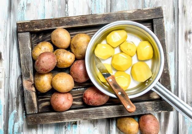 Batatas descascadas em uma panela com batatas com casca na bandeja com uma faca. em madeira