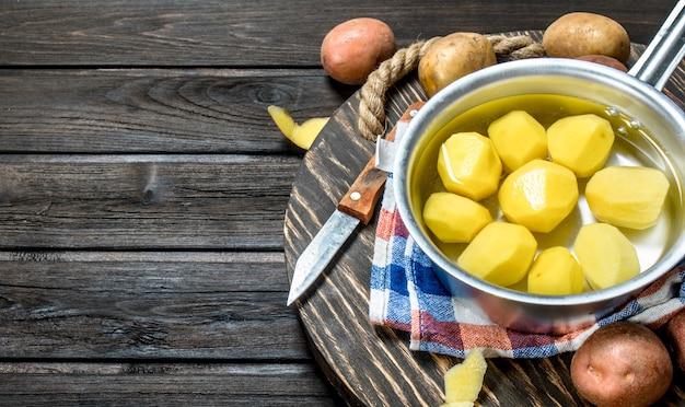 Batatas descascadas em uma panela com batatas frescas na bandeja com uma faca. em fundo de madeira