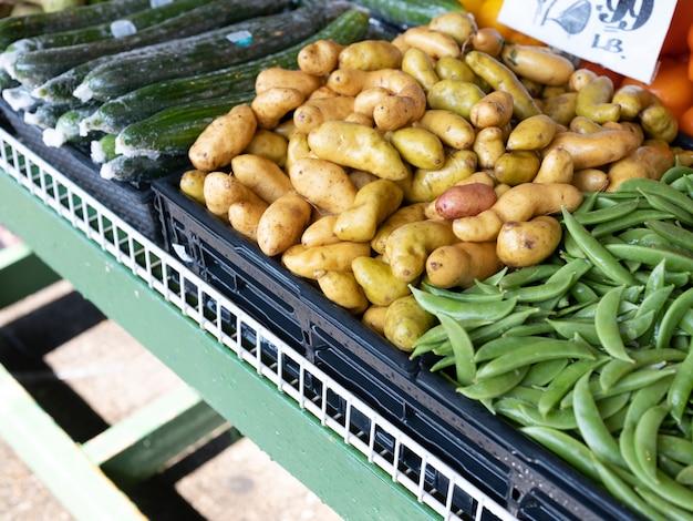 Batatas e vegetais orgânicos frescos em barraca para venda no mercado