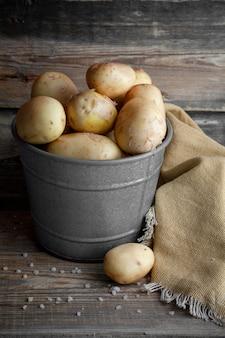 Batatas em um balde cinza sobre um fundo escuro de madeira. vista lateral.