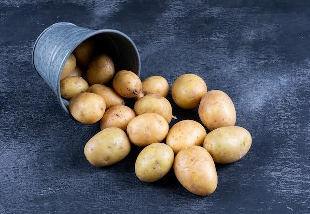 Batatas em um balde de alto ângulo vista sobre uma mesa escura