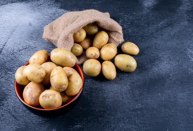 Batatas em um saco de saco e tigela em uma mesa escura