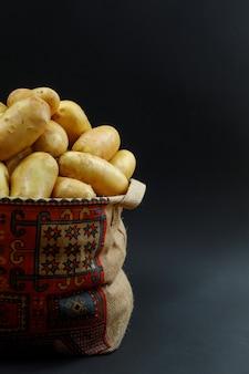 Batatas em um saco estampado em uma mesa escura. vista lateral.